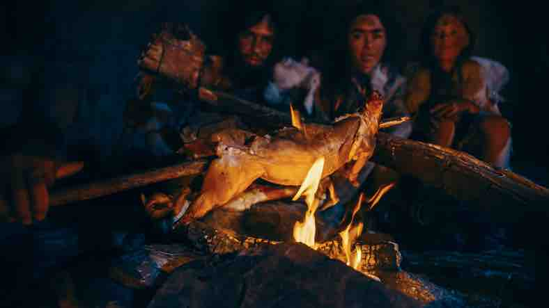 Cavemen cooking meat on a fire