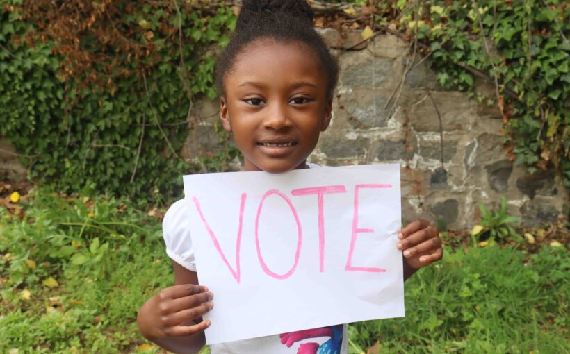 cute kid holding vote sign